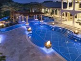 Luxury Pool With Fire PotsPhoto By: Joe TrainaThis home's water features put…